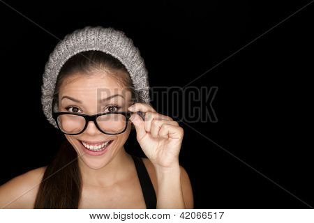 Cool hipster student woman wearing eyewear glasses and knit hat isolated on black background Multiracial mixed race Asian Chinese / Caucasian female university student looking at camera smiling happy.
