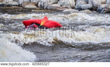kayaker rolling after surfing a wave in the Poudre River Whitewater Park in downtown of Fort Collins