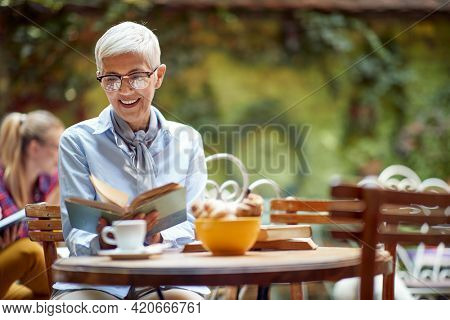 An older woman reading a book while having a coffee in a relaxed atmosphere in the bar. Leisure, bar, outdoor