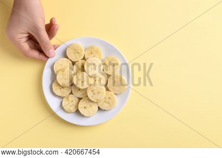 Sliced Banana Fruit Holding By Hand On Yellow Background, Food Ingredients, Tropical Fruit