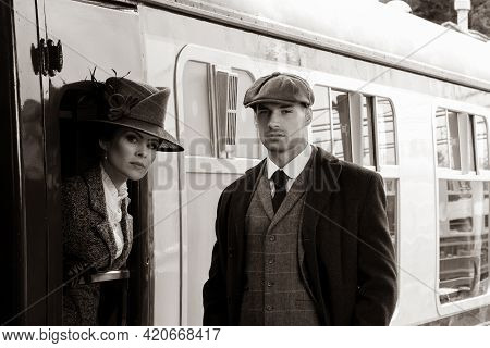 Beautiful Woman Dressed In Vintage 1920s Costume Arriving By Train And Greeted By Her Bodyguard
