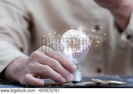 Businessman Hand Holding Light Bulb, Concept Of New Ideas For Business And Finance, Idea Concept Wit