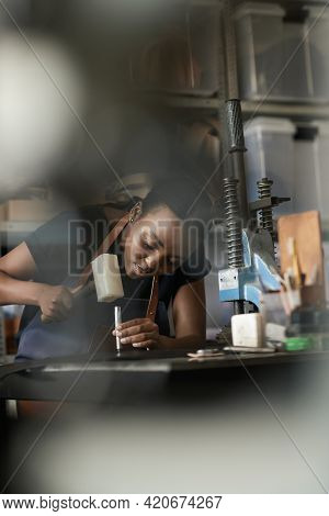 Young African Female Artisan Using A Mallet And Punch On Leather