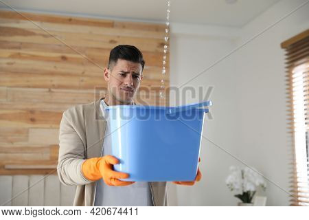 Emotional Man Collecting Water Leaking From Ceiling Indoors. Damaged Roof
