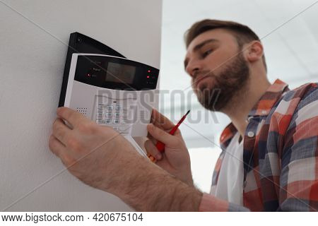 Man Installing Home Security System On White Wall In Room