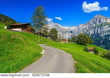 Wooden Buildings And Chalets On The Slope. Narrow Rural Road On The Hill And Snowy Mountains In Back