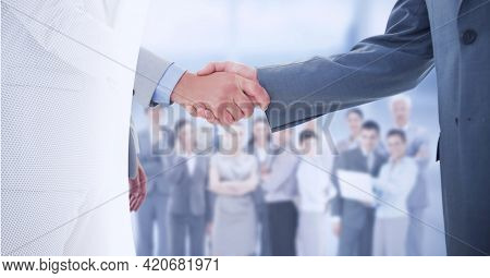 Mid section of two businessmen shaking hands against business people standing in background. global business and technology concept