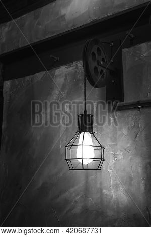 A Lamp With A Metal Frame Hanging In A London Pub. The Lamp Is Attached To An Old Pulley.