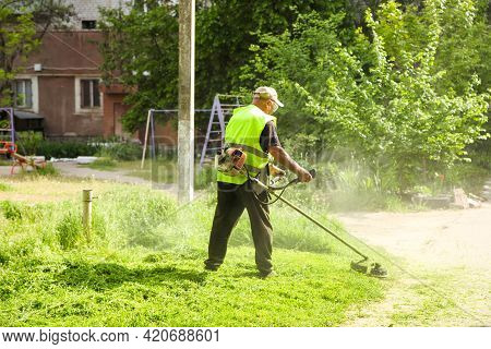 Mower With A Brushcutter. Mowing Grass. Provision Of Services.
