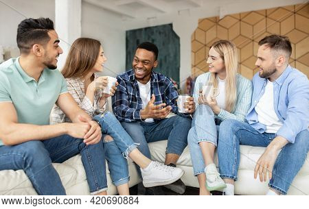 Group Of Cheerful Multiethnic Friends Having Party At Home, Sitting On Couch, Drinking Coffee