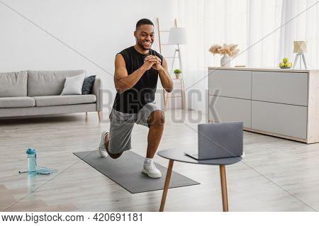 African Man Doing Forward Lunge Exercise Watching Online Workout Indoor