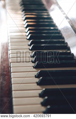 Black And White Piano Keys Close Up. Musical Instrument In The Rays Of The Sun. Side View