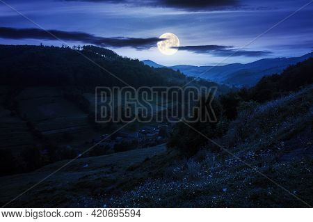 Rural Valley Landscape At Night. Beautiful Carpathian Nature Scenery With Grassy Hills, Fields And M