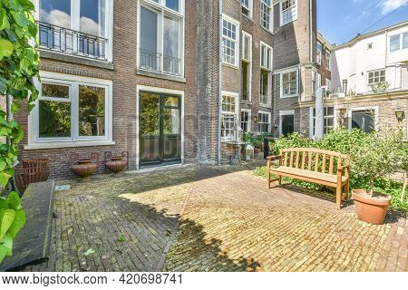 Amsterdam, Netherlands - 22 May, 2020: House Cobblestone Terrace With Benches And Brick Wall Overgro