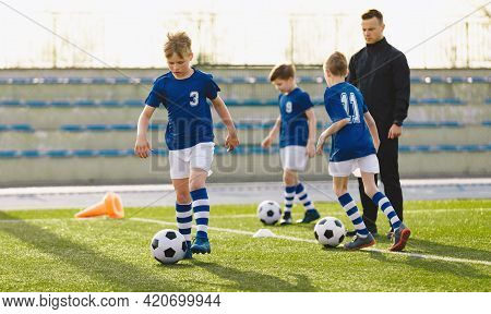 Young Sports Boys In Blue Sportswear Running And Kicking A Ball On The Pitch. The Soccer Youth Team