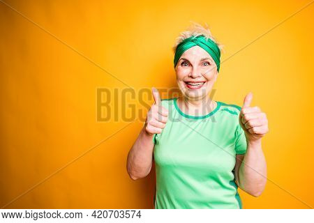 Beautiful Adult Woman With Sports Armband Smiling And Raising Thumbs Up While Standing Against Yello