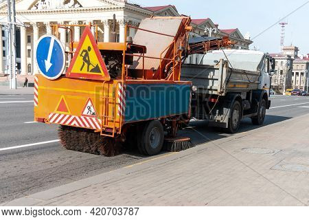 Sweeper In The Process Of Cleaning The Street. Street Cleaning. The Municipal Service Is Cleaning Up