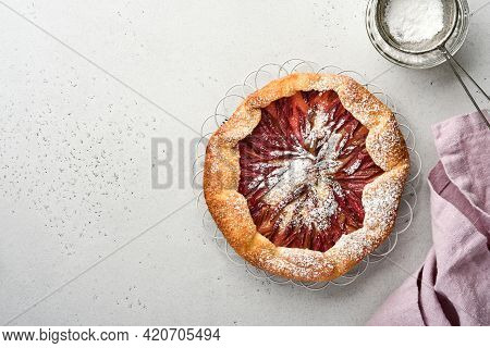 Homemade Rhubarb Galette Made With Star Pattern On Old Concrete Table Background. Process Of Baking.