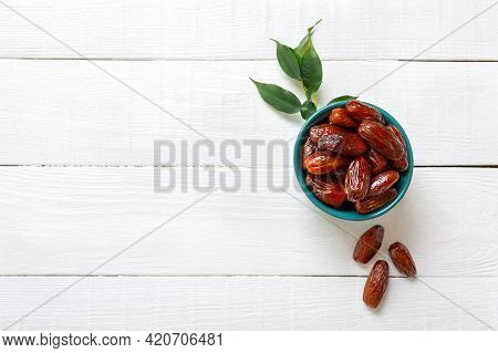 Organic Sun Dried Dates In Ceramic Bowl On A White Wooden Background. Useful Products, Dried Fruits.