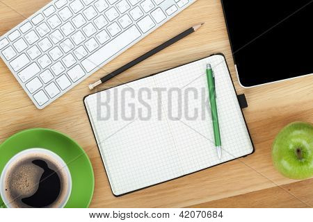 Office supplies, devices, coffee cup and apple on wooden table