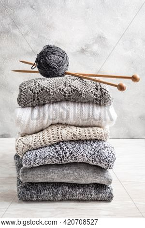 Stack of cozy knitted sweaters and pullovers with knitting needles on wooden background. Autumn and winter concept