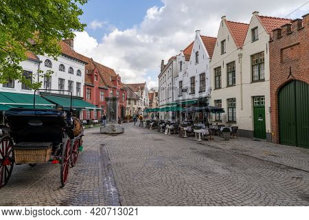 The Historic Old Town Of Brugge With Horse-drawn Carriages And Brick Buildings
