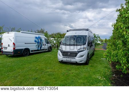 Kruiningen, Neetherlands - 12 May, 2021: Two Camper Vans Parked In A Green Field Of An Rv Park In Ho