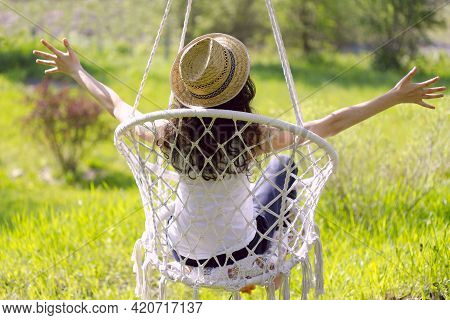 Summer, Emotions. Girl In A Hat On A Hanging Chair In The Garden. The Girl Enjoys A Summer Day.