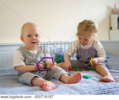 Cute Little Children Infant Boy And Toddler Girl Having Fun While Playing With Toy Construction Set