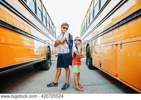Back To School. Caucasian Brothers Students Standing By Yellow School Bus. Cool Kids In Sunglasses G