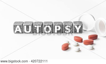Word Autopsy Is Made Of Stone Cubes On A White Background With Pills. Medical Concept Of Treatment,