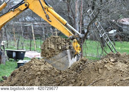 A Road Excavator Dredges The Ground Foundations Near The House