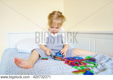 Concentrated Little Girl With Golden Hair Playing With Educational Toy Magnetic Constructor On Bed,