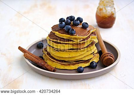 Pumpkin Pancakes With Blueberries And Honey On A Brown Clay Plate On A Light Concrete Background. Am