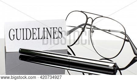 Text Guidelines On Paper On Light Background With Pen And Glasses. Business
