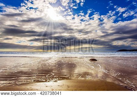Moeraki's huge round boulder on a sandy beach. The Pacific ocean tide begins. New Zealand. The sun's rays are reflected in the ocean water. The concept of ecological, exotic and phototourism