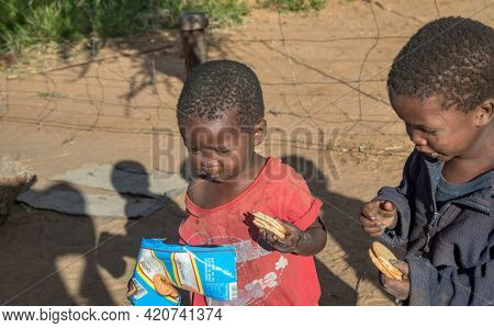 Portrait of an hungry African children eating in their yard in a village  in Botswana village
