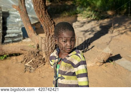African child with a tough look standing in his yard in a village in Botswana
