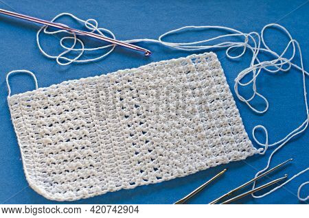 Handmade Crocheted With White Cotton Threads On A Blue Background.