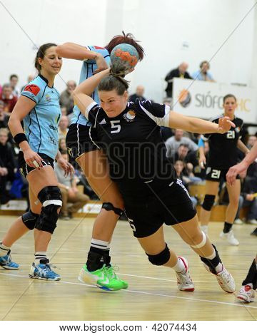 SIOFOK, HUNGARY - FEBRUARY 9: Agnes Szabadfi (black 5) in action at a Hungarian National Championship handball match Siofok KC (black) vs. Fehervar KC (blue) February 9, 2013 in Siofok, Hungary.