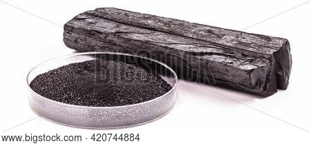 Petri Dish With Powdered Charcoal Next To Piece Of Charcoal, Isolated White Background