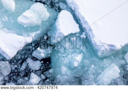 Aerial view of the Arctic Sea alongside the coast of Svalbard. Overhead drone detail of the broken snow-covered pack ice and iceberg fragments.