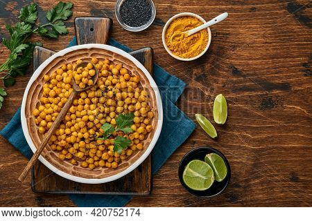 Fried Chickpeas With Turmeric In Ceramic Plate On An Old Wooden Table Background. Roasted Spicy Chic