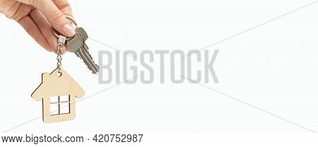 Close-up Of Hand Holds Keys With A House Shaped Keyring, Agent Gives The Key To A New Apartment, On