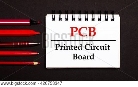 A White Notepad With The Text Pcb Printed Circuit Board, Written On A White Notepad Next To Red Pens