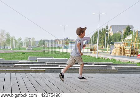 Boy Runs On The Veranda In The Street. Happy And Active Childhood Of The Child. Boy Running On The W