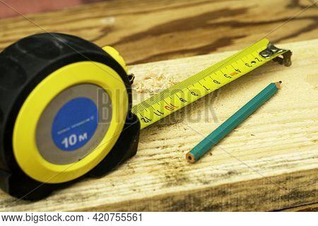 Unfolded Measuring Tape On A Wooden Board