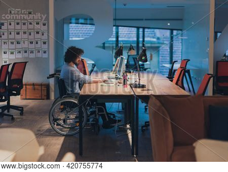 Disabled businessman in wheelchair working overtime alone at his desk in an office late at night