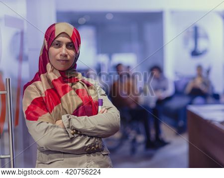 Muslim woman wearing hijab in office, Arabic business woman covered with headscarf smiling. Successful Arab businesswoman in modern office.