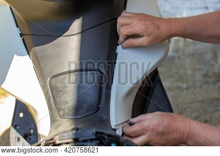 Repair And Dismantling Of A Motorcycle. A Man Removes The Front Side Trim On A Motorbike.